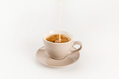 Milk pouring into cup of coffee isolated on white. Close-up view of milk pouring into cup of coffee isolated on white Stock Photos