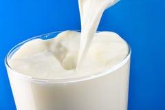 Milk pouring into glass Stock Photos