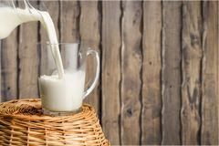 Milk pouring in glass on  background Stock Photos
