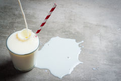 Milk pouring into glass on a concrete table royalty free stock photography