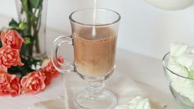Milk pouring a glass cup of coffee. Orange roses and marshmallows on white background stock footage
