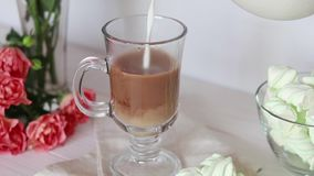 Milk pouring a glass cup of coffee stock footage