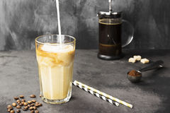 Milk pouring in ice coffee in a tall glass on a dark background. Copy space. Food background.  Stock Photos