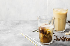 Milk pouring in ice coffee in a tall glass on a gray background. Copy space. Food background. Toning Stock Images