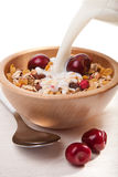 Milk pouring onto cereal with berries isolated Stock Image