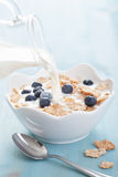 Milk pouring onto cornflakes with blueberry Royalty Free Stock Photos