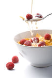 Milk pouring onto muesli with raspberry Royalty Free Stock Image