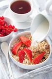 Milk pouring over granola with strawberry for breakfast Royalty Free Stock Photo