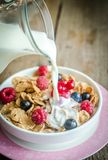 Milk pouring into plate with granola and fresh berries Stock Photos