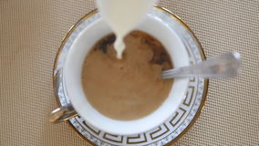 Milk pouring into tea. Close up slow motion stock footage