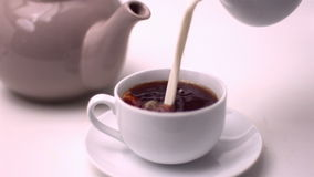 Milk pouring into tea stock footage