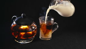 Milk pouring into tea in a transparent Cup.  stock video footage