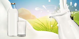 Milk pouring in transparent glass jug on bright background Stock Photo
