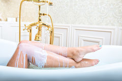 Milk pouring on woman legs royalty free stock images