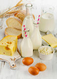 Milk products, bread and eggs on a wooden table. Stock Photos