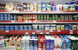 Milk products on shelves. Shelves with milk products are displayed in the aisle inside a supermarket
