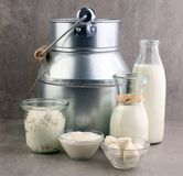 Milk products - tasty healthy dairy products on a table on: sour cream in a white bowl, cottage cheese bowl, cream in a a bank and. Milk jar, glass bottle and Royalty Free Stock Photos