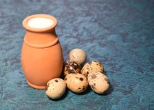 Milk and quail eggs. On a dark blue background Stock Images