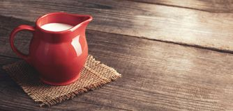 Milk in red pitcher on white background wooden table.  royalty free stock images