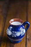 Milk in a rustic cup. Milk in a traditional Romanian rustic cup Royalty Free Stock Photo