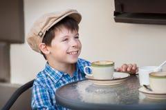 Milk shake bebendo do rapaz pequeno no café Imagem de Stock