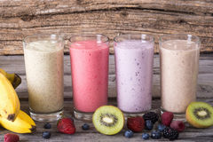 Milk shake with berries. And fruit on wooden background royalty free stock image