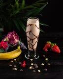 Milk shake com banana e chocolate em um vidro alto em um fundo escuro foto de stock