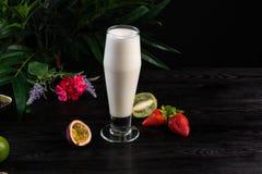 Milk shake em um vidro alto e em frutos em um fundo escuro fotos de stock royalty free