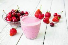 Milk shake feito da mistura - cereja e morango e bagas saborosos na tabela de madeira branca fotografia de stock