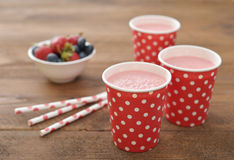 Milk shake with fresh berries. And straws on wooden background Royalty Free Stock Photography