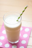 Milk shake with striped straw on polka dot napkin Royalty Free Stock Photos