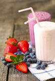 Milk shakes and fresh berries on a dark wooden background Stock Photography