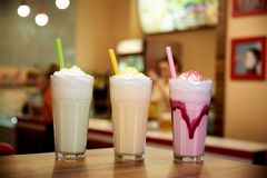 Milk shakes with straws on a wooden table in a cafe. Milk shakes with straws on wooden table in a cafe stock photography