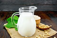 Milk soy in jug with flour on dark board. Soy milk in a jug, flour in a bowl and a fresh green leaf, soybeans in a spoon and burlap on the background of a dark stock photo