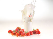 Milk splash in a glass, milk and a strawberry on a white backgro. Und royalty free stock photos