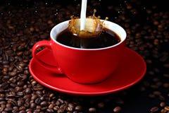 Milk splashing into coffee. Milk splashing into red cup of coffee stock image
