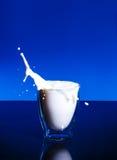 Milk splashing in glass blue background. Milk splashing in glass on a blue background with reflection Royalty Free Stock Photos