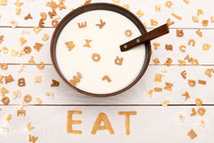 Milk and spoon in bowl, word eat from breakfast cereal letters and alphabet corn flakes on wooden table Royalty Free Stock Photos
