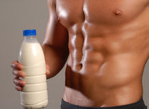 Milk sport. Shaped and healthy body man holding a milk bottle Stock Photography