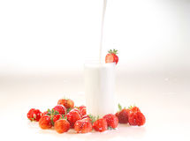 Milk and strawberry on a white background, milk flows in a trans. Parent glass royalty free stock photography