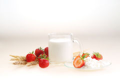 Milk and strawberry on a white background, milk in a transparent. Mug and cottage cheese with a strawberry royalty free stock photos