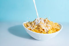 Milk stream jet pouring into a bowl with yellow flakes, milk splashes on a blue celestial background Stock Image
