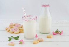 Milk with sugar sprinkles and cookie hearts Stock Images