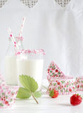Milk with sugar sprinkles, strawberries and cupcake wrapper Royalty Free Stock Photography