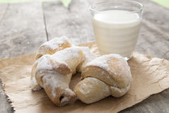 Milk and sweet rolls with sugar on a wooden background Royalty Free Stock Photos