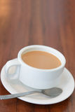 Milk tea. Cup of hot milk tea with spoon on table Royalty Free Stock Photography