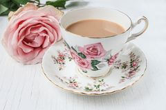 Milk tea in a china cup and saucer, with pink roses. Tea in a china cup and saucer, with pink rose pattern and pink cut rose. On a white, painted, distressed Stock Photo