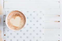 Milk tea with heart made of cinnamon on a white wooden background stock images
