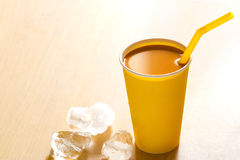 Milk tea in paper cup and ice on wooden background. Warm color tone Stock Photo