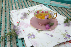 Milk thistle herbal tea. A cup of milk thistle tea on a table cloth. Milk thistle blossoms are in the background royalty free stock image